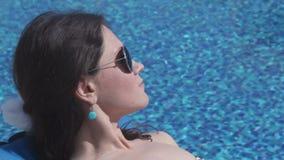 Młody atrakcyjny kurczątko w okularach przeciwsłonecznych cieszy się odpoczynek przy poolside zdjęcie wideo