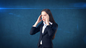 Młody atrakcyjny longhair bizneswoman w kostiumu stresującym się i trzyma jej głowę w zmęczeniu, odosobniony pracowniany tło Fotografia Stock