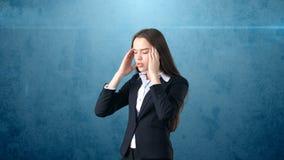 Młody atrakcyjny longhair bizneswoman w kostiumu stresującym się i trzyma jej głowę w zmęczeniu, odosobniony pracowniany tło Zdjęcie Royalty Free