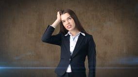 Młody atrakcyjny longhair bizneswoman w kostiumu stresującym się i trzyma jej głowę w zmęczeniu, pracowniany tło Obraz Stock