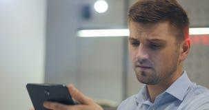 Młody atrakcyjny mądrze biznesmena prawnika lekarki kierownika urzędnik emocjonalnie używa jego pastylka komputer osobistego w bi zbiory wideo
