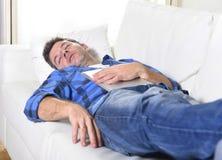 Młody atrakcyjny mężczyzna śpi w domu leżankę relaksuje po pracować z cyfrowym pastylka ochraniaczem Fotografia Royalty Free