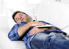 Młody atrakcyjny mężczyzna śpi w domu leżankę relaksuje po pracować z cyfrowym pastylka ochraniaczem Fotografia Stock