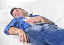 Młody atrakcyjny mężczyzna śpi w domu leżankę relaksuje po pracować z cyfrowym pastylka ochraniaczem Zdjęcia Stock
