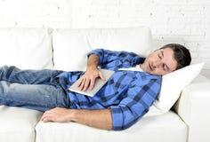 Młody atrakcyjny mężczyzna śpi w domu leżankę relaksuje po pracować z cyfrowym pastylka ochraniaczem Zdjęcie Royalty Free