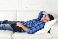 Młody atrakcyjny mężczyzna śpi w domu leżankę relaksuje po pracować z cyfrowym pastylka ochraniaczem Obraz Stock