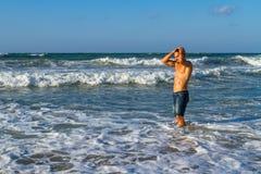 Młody atrakcyjny mężczyzna cieszy się spalshing w oceanie Obrazy Royalty Free