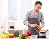 Młody atrakcyjny mężczyzna kucharstwo w kuchni obraz royalty free