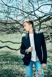 Młody atrakcyjny mężczyzna w białej koszulce i niebieskich dżinsach obrazy royalty free