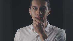 Młody atrakcyjny mężczyzna w białej koszulowej patrzeje kamerze odizolowywającej na czarnym tle zbiory