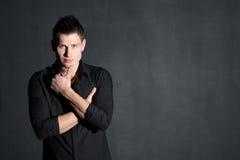 Młody atrakcyjny mężczyzna w czarnej koszula na ciemnym tle obrazy royalty free