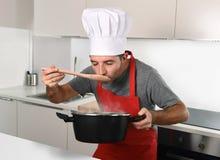 Młody atrakcyjny mężczyzna w szefa kuchni kapeluszu i czerwień fartucha testowanie kucbarskim smaku Zdjęcie Royalty Free