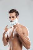 Młody atrakcyjny mężczyzna z golenie pianą na twarzy wskazywać fotografia stock