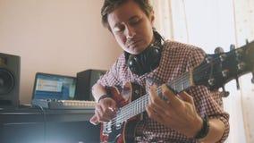 Młody atrakcyjny męski muzyk komponuje ścieżkę dźwiękowa bawić się gitarę i nagrywa używać komputer, ostrość na twarzy i zdjęcie stock