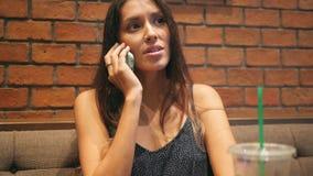 Młody Atrakcyjny Mieszany Biegowy dziewczyny mówienie na telefonie komórkowym i Pić Matcha zielonej herbaty w sklep z kawą 4K Taj zbiory