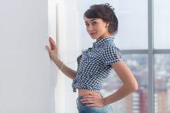 Młody atrakcyjny model z dysponowanym ciałem pozuje w lekkim studiu, będący ubranym cajgi i błękitną w kratkę koszula, stać z uko Obraz Royalty Free