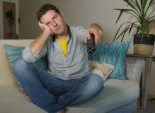 Młody atrakcyjny nieszczęśliwy mężczyzna trzyma ponowny w przypadkowych ubraniach zanudzających i udaremniających w domu oglądają zdjęcie royalty free