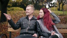 Młody atrakcyjny pary obsiadanie na ławce w jesieni opowiadać i parku Atrakcyjna kobieta z czerwonym włosy dymi zbiory