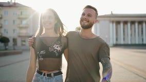 Młody atrakcyjny pary odprowadzenia puszek ulica wpólnie i ono uśmiecha się w zwolnionym tempie od 100fps zbiory