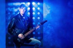 Młody atrakcyjny rockowy muzyk bawić się gitarę elektryczną i śpiew Gwiazda rocka na tle światła reflektorów Obraz Stock