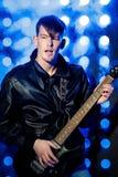 Młody atrakcyjny rockowy muzyk bawić się gitarę elektryczną i śpiew Gwiazda rocka na tle światła reflektorów Zdjęcie Royalty Free