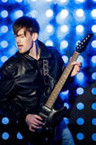 Młody atrakcyjny rockowy muzyk bawić się gitarę elektryczną i śpiew Gwiazda rocka na tle światła reflektorów Fotografia Royalty Free