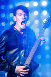 Młody atrakcyjny rockowy muzyk bawić się gitarę elektryczną i śpiew Gwiazda rocka na tle światła reflektorów fotografia stock