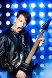 Młody atrakcyjny rockowy muzyk bawić się gitarę elektryczną i śpiew Gwiazda rocka na tle światła reflektorów zdjęcia royalty free