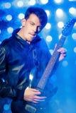 Młody atrakcyjny rockowy muzyk bawić się gitarę elektryczną i śpiew Gwiazda rocka na tle światła reflektorów obraz royalty free