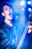 Młody atrakcyjny rockowy muzyk bawić się gitarę elektryczną i śpiew Gwiazda rocka na tle światła reflektorów Obrazy Royalty Free