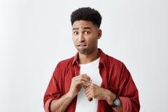Młody atrakcyjny skinned mężczyzna z afro fryzurą w przypadkowych eleganckich odzieżowych mienie rękach wpólnie, patrzejący wewną zdjęcie stock