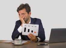 Młody atrakcyjny smutny i przygnębiony biznesmen pracuje w stresie przy biurowego komputeru biurkiem pokazuje sprzedaży korzyści  obrazy stock