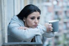 Młody atrakcyjny smutny kobiety cierpienie od depresji pije filiżankę kawy na balkonie w domu fotografia stock