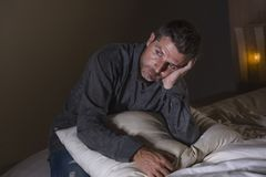 Młody atrakcyjny smutny, przygnębiony mężczyzna na i łóżkowym cierpienie niepokoju kryzysie przytłaczającym i stresującym się obraz stock