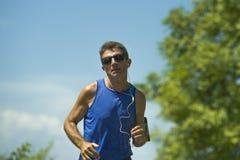 Młody atrakcyjny sporta biegacza mężczyzna szkolenie w asfaltowej drogi działającym treningu pogodny lato ranek otaczający drzewa obrazy royalty free