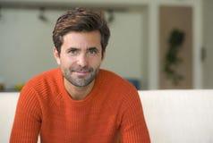 Młody atrakcyjny, szczęśliwy 30s mężczyzna uśmiecha się obsiadanie przy żywą izbową kanapy leżanką w jego nowożytnej mieszkanie o zdjęcia royalty free
