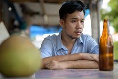 Młody Azjatycki alkoholiczny mężczyzna pije piwo w ulicach outdoors obrazy royalty free