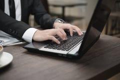Młody Azjatycki biznesmen pracuje z laptopem w sklep z kawą zdjęcia royalty free
