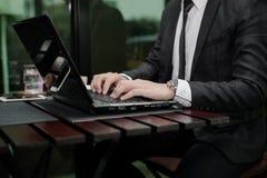 Młody Azjatycki biznesmen pracuje z laptopem w sklep z kawą zdjęcia stock