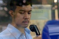 Młody Azjatycki biznesmen używa payphone outdoors zdjęcie royalty free