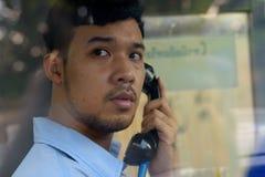 Młody Azjatycki biznesmen używa payphone outdoors zdjęcie stock