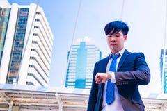 Młody Azjatycki biznesmen w miasteczku biznesmen widzii zegarek obrazy stock