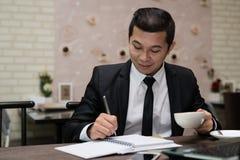 Młody Azjatycki biznesmena writing zauważa obsiadanie w sklep z kawą fotografia royalty free