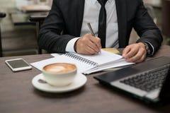 Młody Azjatycki biznesmena writing zauważa obsiadanie w sklep z kawą fotografia stock