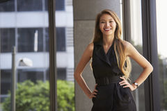 Młody Azjatycki bizneswoman patrzeje kamera, ręki na biodrach zdjęcie royalty free
