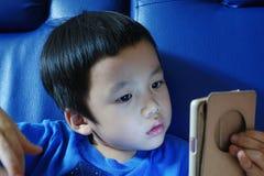 Młody Azjatycki dzieciak gapi się przy telefonem z błękitnym tłem Obraz Royalty Free