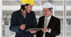 Młody Azjatycki inżynier używa pastylkę przedstawiać jego pracę kierownik wyższego szczebla inżynier w przemysłowej fabryce zbiory