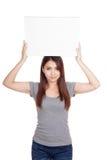 Młody Azjatycki kobieta chwyta puste miejsce podpisuje jej głowę Zdjęcia Stock