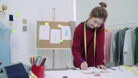 Młody Azjatycki kobieta projektanta mody rysunku używać ołówkowy i patrzeć papier w warsztatowym studiu podczas gdy pracujący zbiory wideo