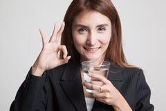 Młody Azjatycki kobiety przedstawienia OK z szkłem woda pitna Obrazy Stock